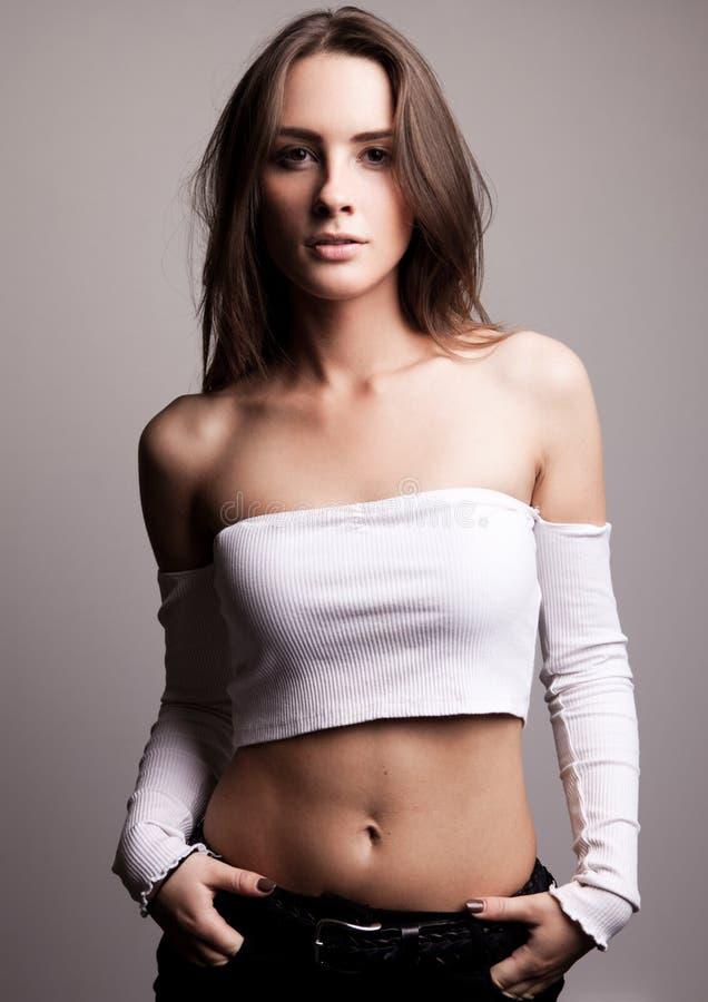 Sexig modell för mode som poserar på grå bakgrund arkivfoto