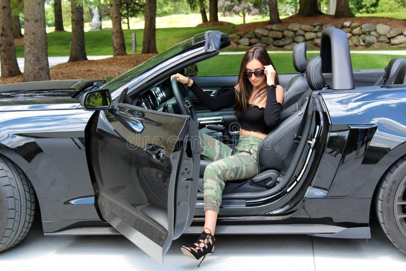 Sexig modell i härlig flicka för sportbil med en bil för muskel för hästkraft för Ford mustangRoush etapp 3 900 HP royaltyfri fotografi