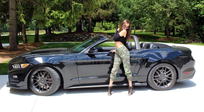 Sexig modell i härlig flicka för sportbil med en bil för muskel för hästkraft för Ford mustangRoush etapp 3 900 HP royaltyfria bilder