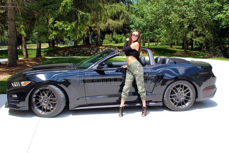 Sexig modell i härlig flicka för sportbil med en bil för muskel för hästkraft för Ford mustangRoush etapp 3 900 HP arkivbild