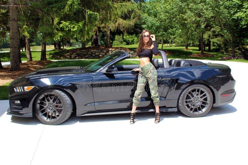 Sexig modell i härlig flicka för sportbil med en bil för muskel för hästkraft för Ford mustangRoush etapp 3 900 HP royaltyfria foton