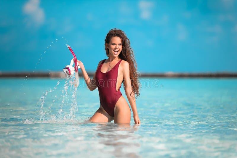 Sexig modell på strandsemester Lyckligt roligt anseende för maskering för dykapparat för flickainnehavsnorkel i havvatten Maldive royaltyfri bild