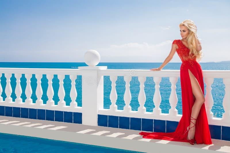 Sexig modell som bär ett långt, rött, aftonklänning som står vid pölen arkivbilder