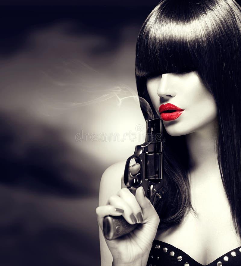 Sexig modellkvinna med ett vapen