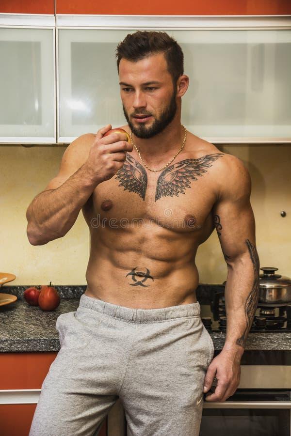 Sexig muscleman i kök som äter äpplet fotografering för bildbyråer