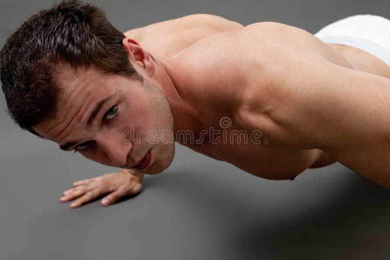Sexig muskulös man som gör kondition arkivbild