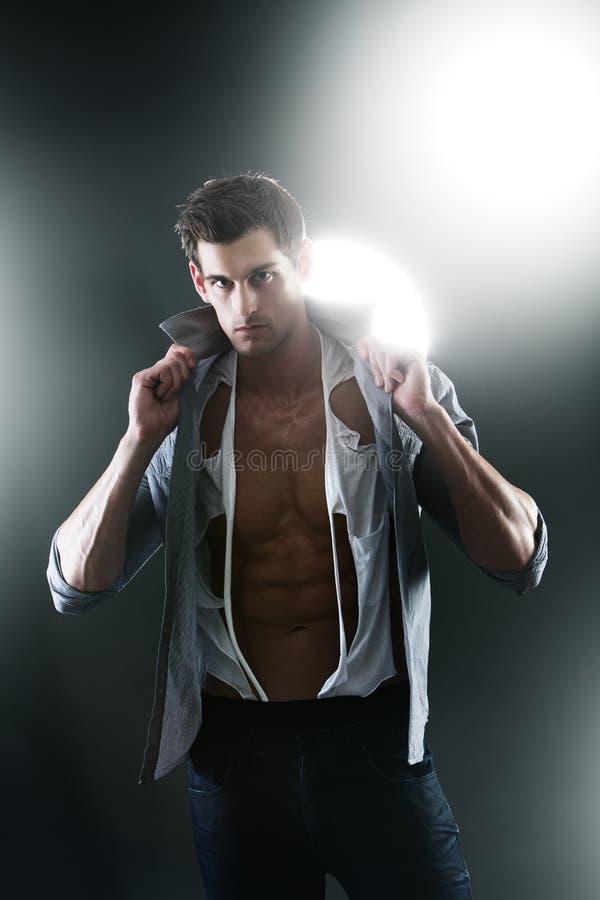 Sexig muskulös manlig i den vita rev sönder skjortan fotografering för bildbyråer