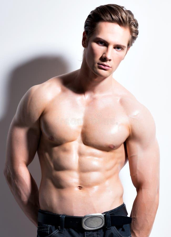Sexig muskulös ung man som ser kameran arkivfoto