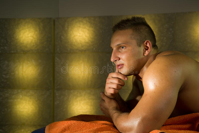 Sexig naken ung man på säng arkivfoton