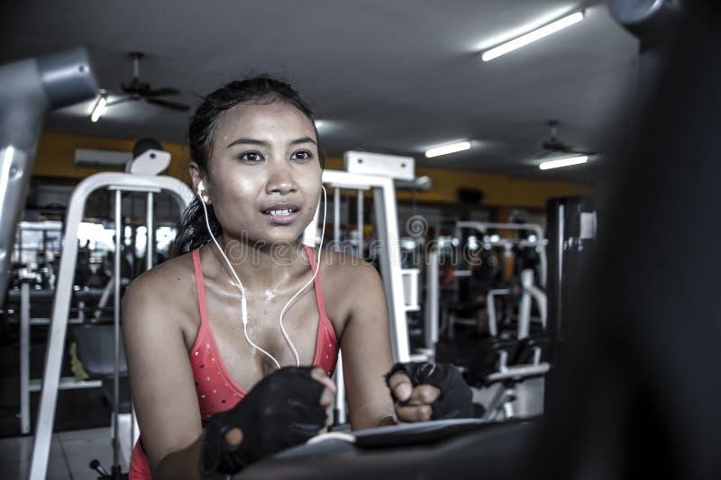 Sexig och svettig asiatisk kvinna som hårt utbildar på idrottshallen genom att använda det ellipsformiga trampa maskinkugghjulet  royaltyfri fotografi