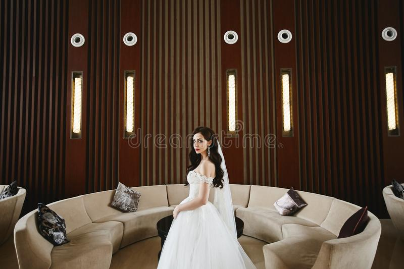 Sexig och ung modellkvinna med den perfekta kroppen och stora bröst i den trendiga bröllopsklänningen med nakna skuldror royaltyfria foton