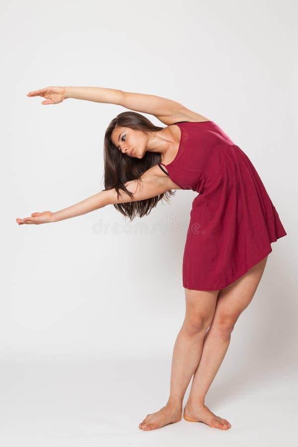 Sexig passformbrunettkvinna i röda klänningsportar fotografering för bildbyråer
