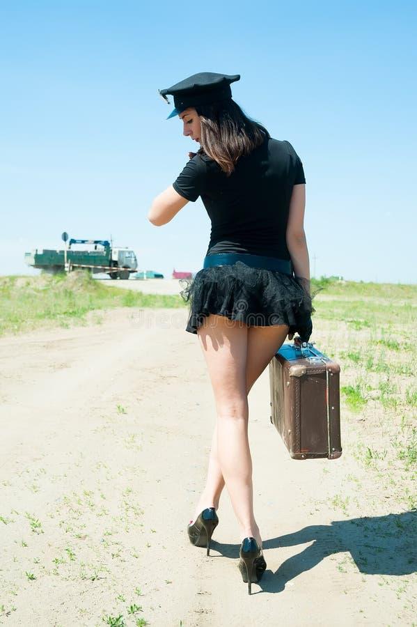 Sexig poliskvinna som går med den gamla resväskan royaltyfri bild