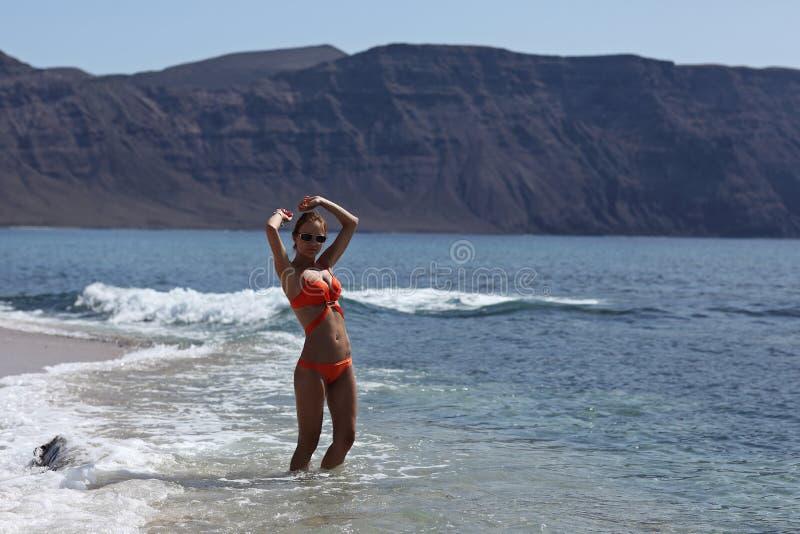 Sexig rödhårig manmodell för perfekt kropp i den orange bikinin som går i havet på papagayostranden kanariefågelöar lanzarote royaltyfri bild
