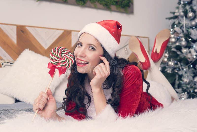 Sexig santa kvinna som slickar klubban på bakgrunden av julgranen En söt julklapp Den nätta kvinnan har gyckel på royaltyfria bilder