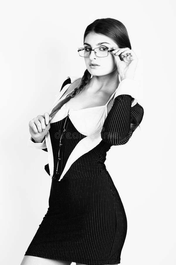 Sexig sekreterare, stående av den härliga brunettaffärsdamen med exponeringsglas och att bära i kritstreckdräkt svart white arkivfoto