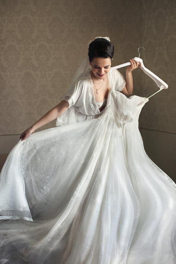 Sexig sinnlig brunettbrud som försöker på bröllopsklänningen royaltyfria foton