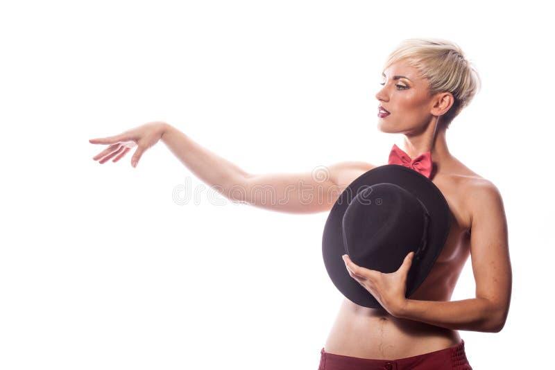 Sexig sinnlig kvinna som täcker henne bröst med en hatt arkivbild