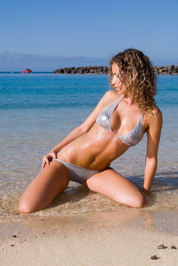 sexig sittande kvinna för bikinisjösida arkivfoto
