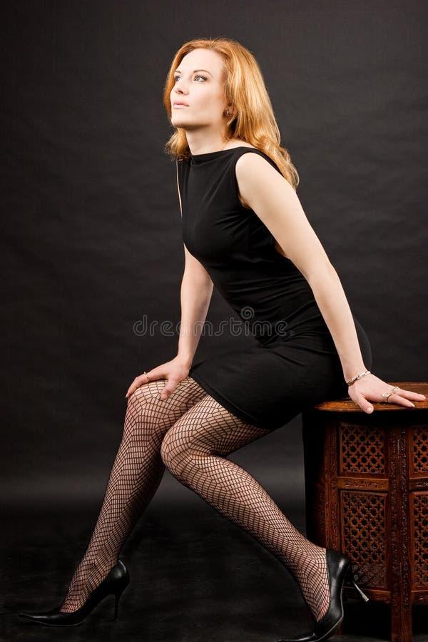 sexig sittande kvinna för redhead royaltyfri foto