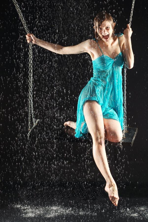 Sexig skrikig flicka i klänningridning på swing royaltyfri fotografi