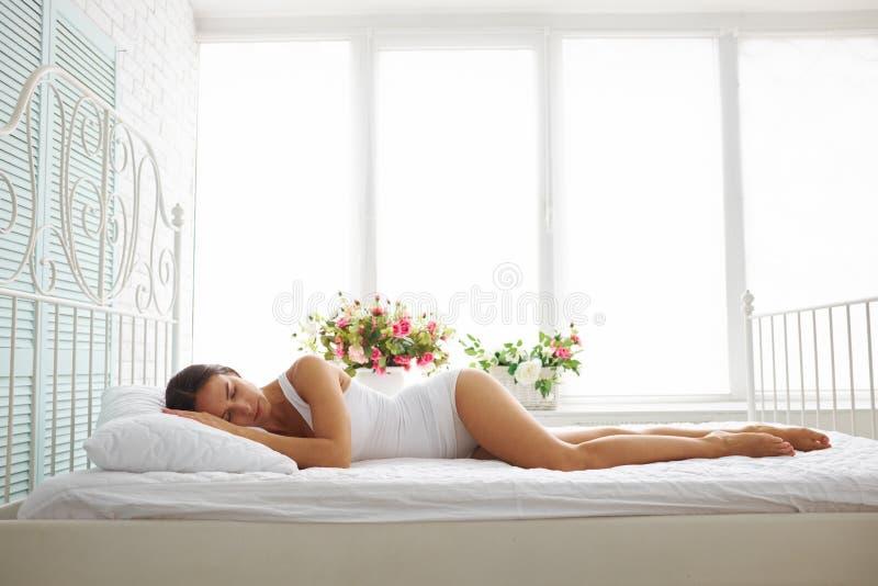 Sexig slank kvinna i den vita underkläderna som sover på säng med vitt sh arkivfoto