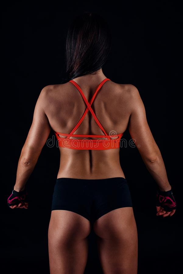 Sexig slank kvinnlig för härlig kondition i activewearen som poserar över svart bakgrund tillbaka sikt royaltyfri bild
