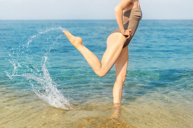 Sexig slank sportig ung vuxen kvinna som gör färgstänk med benet i vatten på havs- eller havstrandsemesterorten Kondition reser o royaltyfri fotografi
