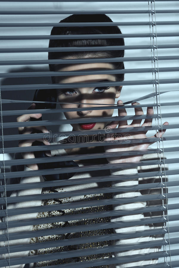 Sexig spionkvinna bak slutare arkivbilder