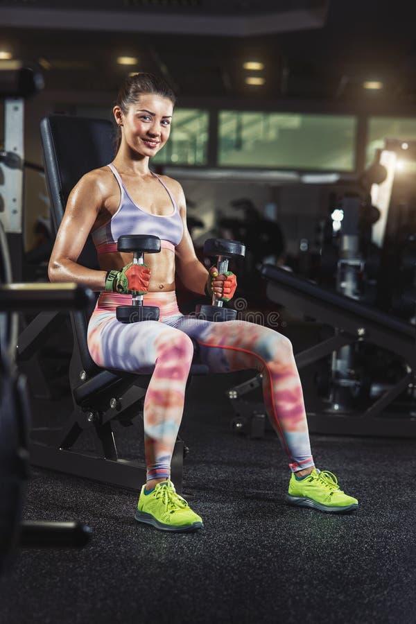 Sexig sportig kvinna som övar i idrottshall med hantlar royaltyfri foto