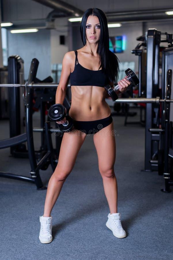 Sexig sportig kvinna som gör maktkonditionövning på sportidrottshallen Härlig flicka som utarbetar i idrottshall royaltyfria foton