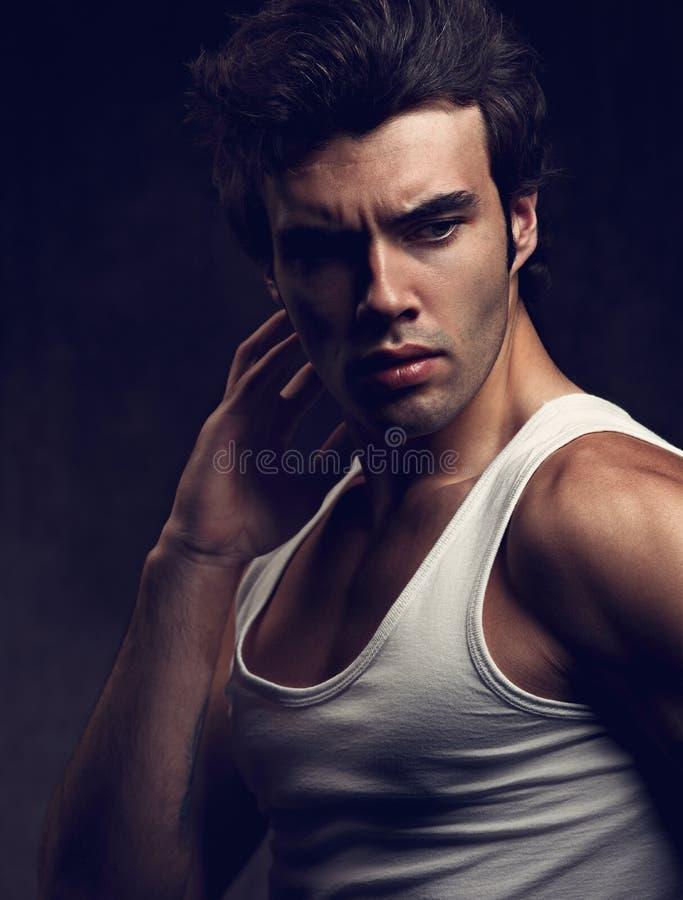 Sexig stark ung stilig man som poserar i den vita t-skjortan på drak s arkivbilder