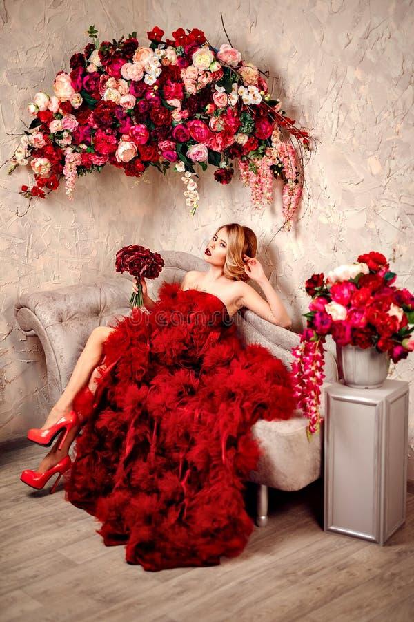 Sexig stilfull blond härlig kvinna på soffan arkivfoto