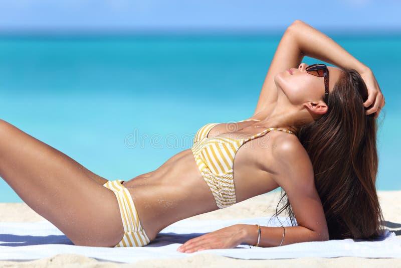 Sexig strandkvinna som solbadar i modebikini royaltyfri foto