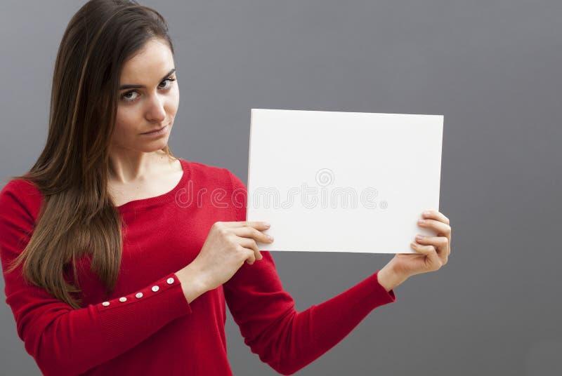 Sexig 20-talflicka med långt brunt hår som rymmer ett meddelande på vit bakgrund royaltyfri foto
