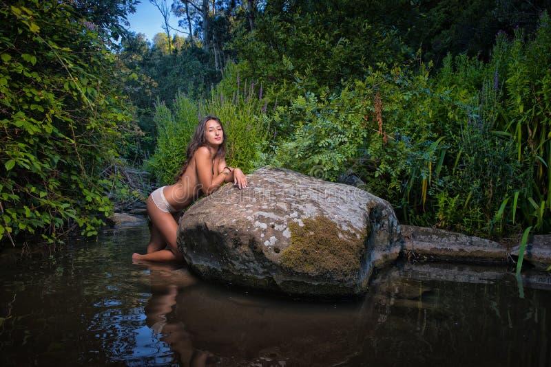 Sexig topless kvinna i floden fotografering för bildbyråer
