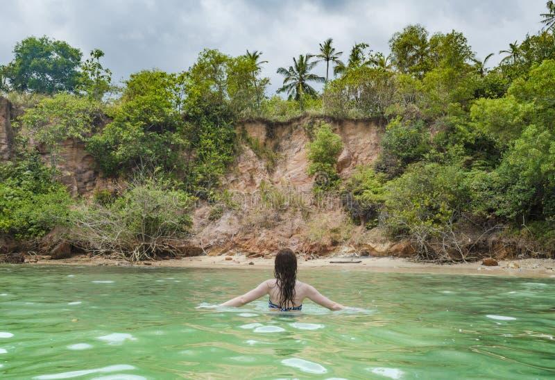 Sexig ung härlig flicka i bikini som går i havet på den tropiska stranden arkivfoton