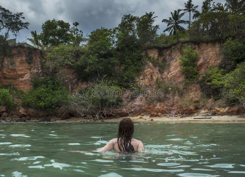 Sexig ung härlig kvinna i bikini som går i havet på den tropiska stranden arkivbilder