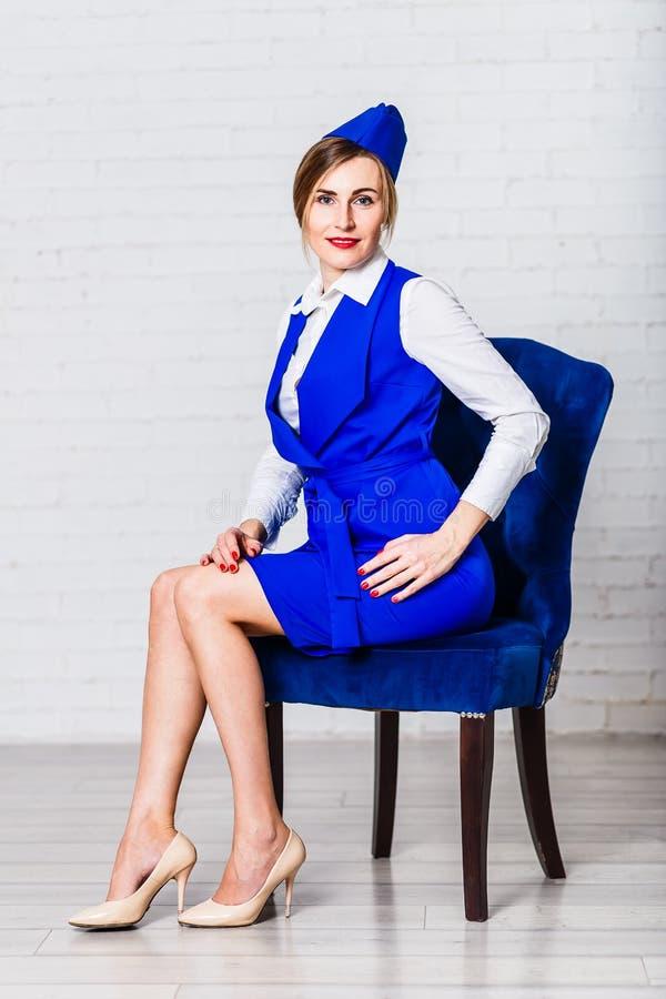 sexig ung kvinna i den blåa stewardessdräkten som sitter på blå stol på vit bakgrund Trettio-år-gammal le kvinna arkivfoton