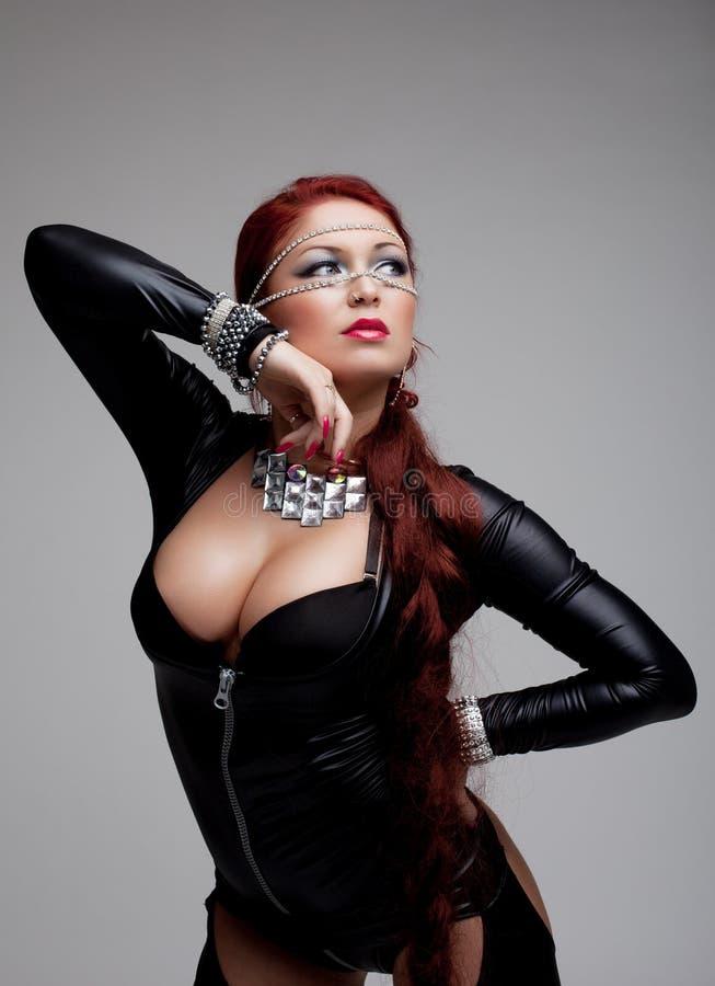 Sexig ung kvinna i latexdräkt med det enorma bröst royaltyfri bild