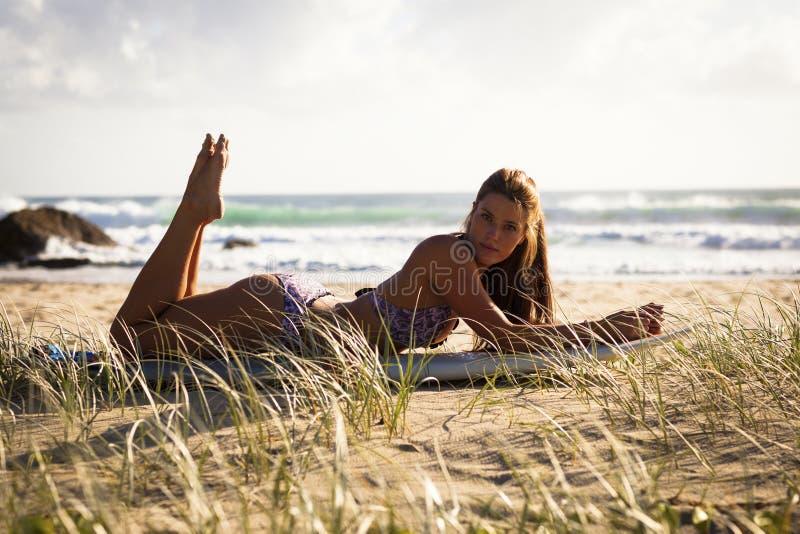 Sexig ung kvinna med surfingbrädan på stranden arkivfoto