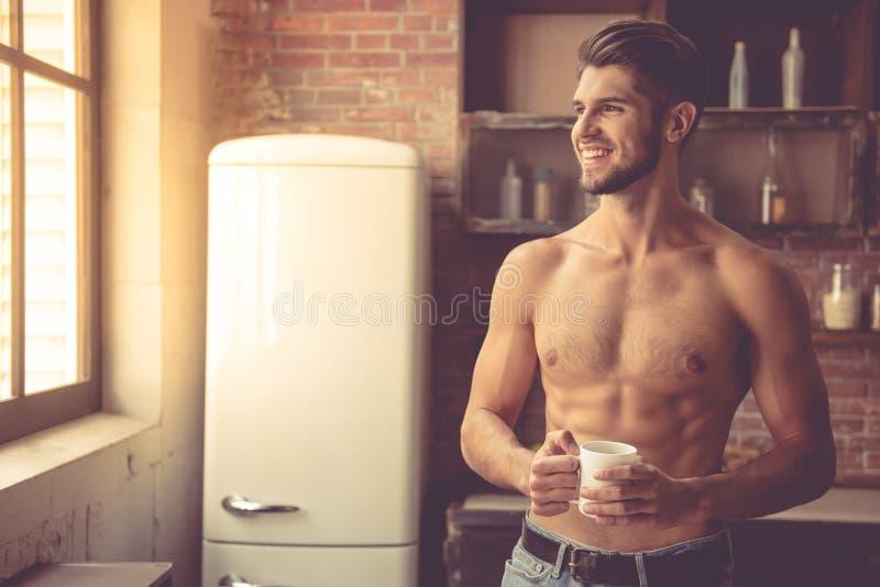 Sexig ung man i kök arkivbild