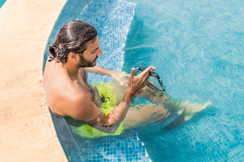 Sexig ung man med skyddsglasögon som kopplar av i simbassängen i en semesterort arkivfoto