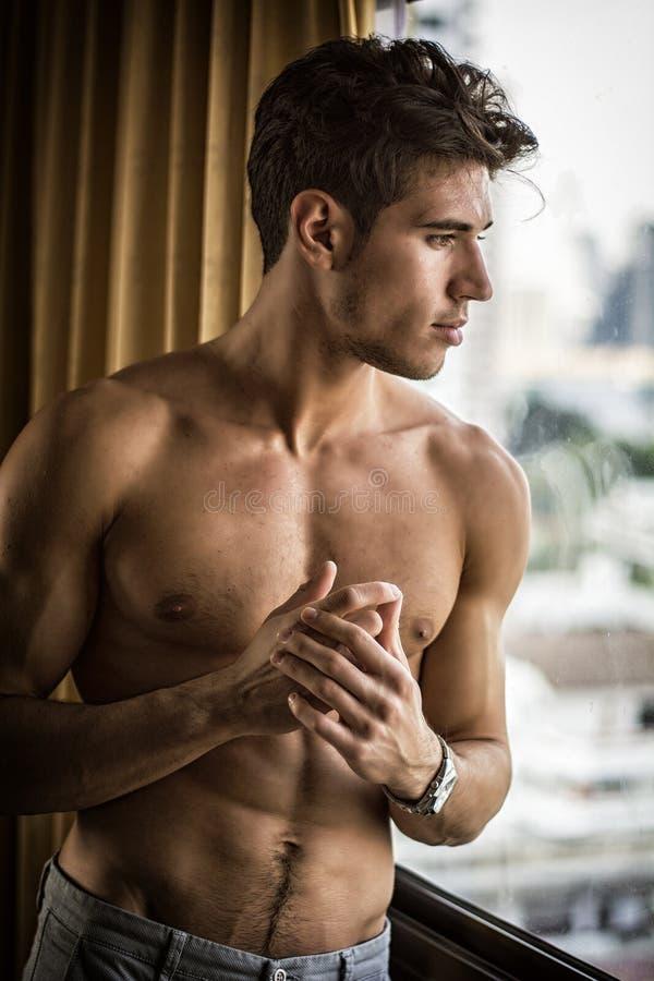 Sexig ung man som st?r shirtless vid gardiner royaltyfria foton