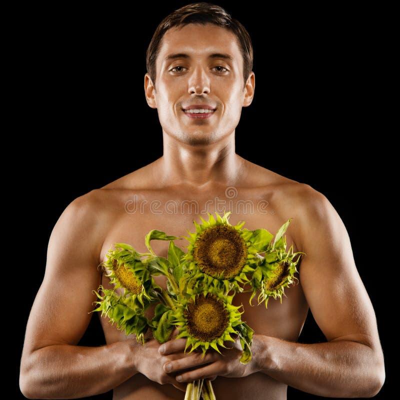 Sexig ung muskulös man med en bukett av blommor arkivbilder