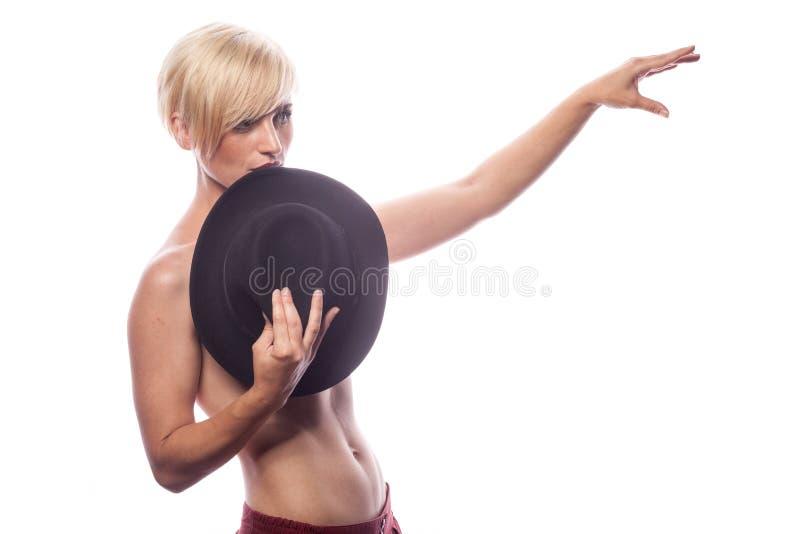 Sexig ursnygg kvinna som täcker henne bröst med en hatt arkivbild