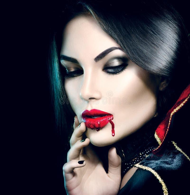 Sexig vampyrflicka med stekflottblod på hennes mun fotografering för bildbyråer