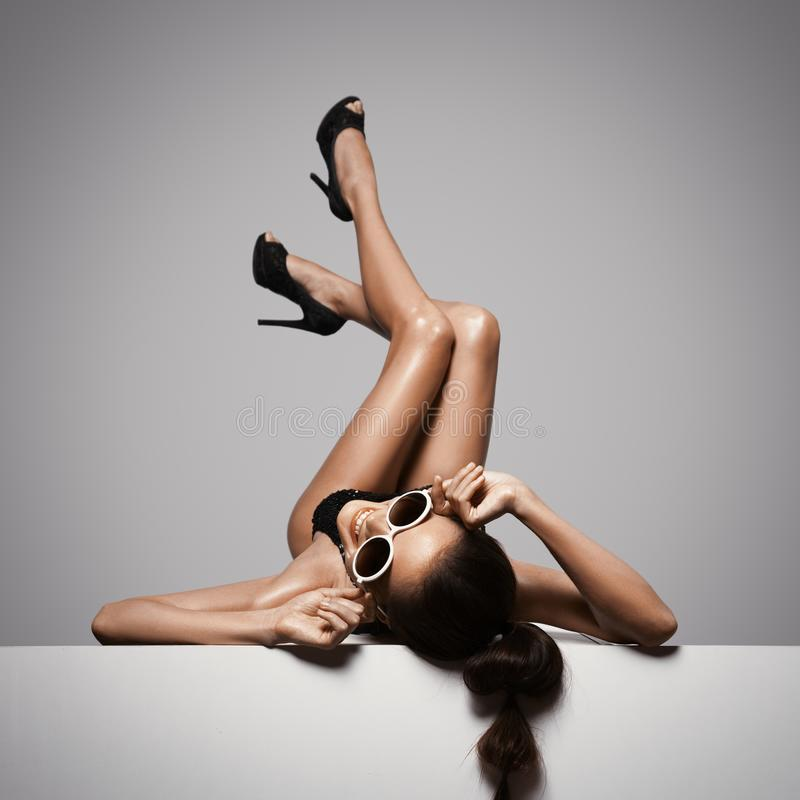 Sexiga ben f?r kvinna i svarta skor Gr? f?rgbakgrund royaltyfri fotografi