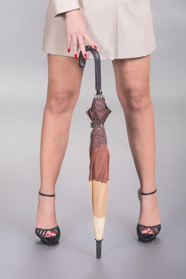 Sexiga ben, häl och paraply arkivfoto