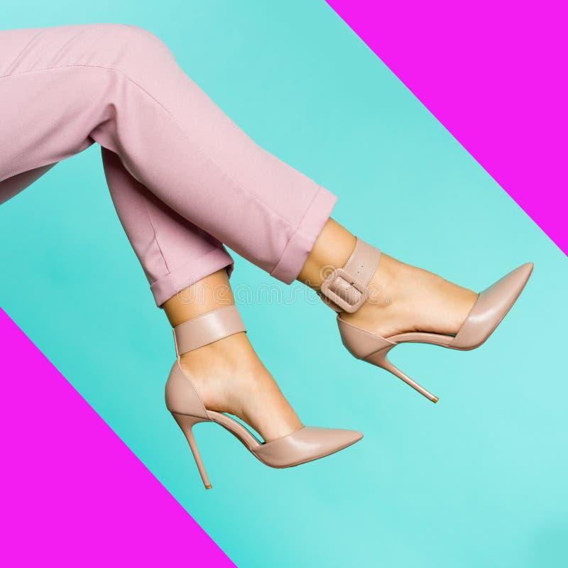 Sexiga ben i bruna skor för höga häl på blå bakgrund arkivfoton